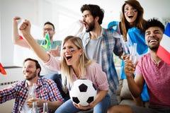 情感地观看比赛的足球迷在客厅 免版税库存照片