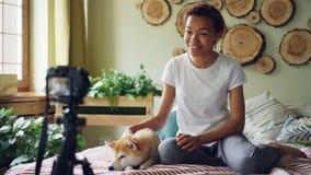 情感女孩成功的博客作者记录她的网上vlog的录影坐在现代公寓和抚摸的床 股票录像