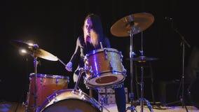 情感女孩鼓手,有吸引力的youngblack头发模型播放鼓 免版税图库摄影