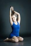 情感妇女画象蓝色短的礼服的坐在黑暗的背景的地板 库存照片