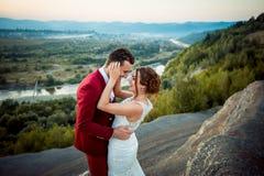 情感婚礼被射击新婚佳偶 愉快的夫妇是微笑和拥抱在美好的风景的背景 库存图片