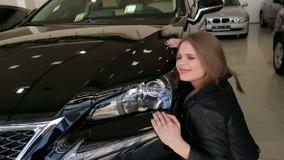 情感年轻女人高兴在一辆新的汽车的购买,她拥抱她的汽车 股票视频