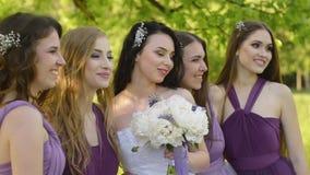 情感微笑新娘和的女傧相谈话和 摆在紫色的礼服的白种人女孩户外 股票录像