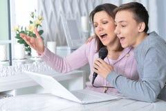 情感母亲和儿子唱歌卡拉OK演唱画象  库存图片
