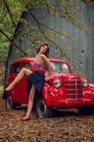 情感纵向 摆在近乘一辆红色俄国减速火箭的汽车的画报女孩 模型大笑,调情地显示苗条腿 免版税库存照片