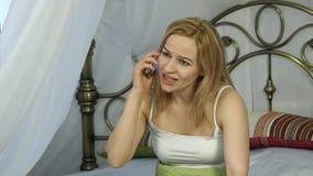情感美丽的白肤金发的妇女在电话在床上唱歌 4K 影视素材