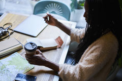 情感美丽的美国黑人的妇女鲜美咖啡和使用现代技术 库存照片