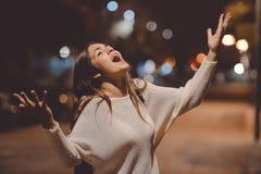 年轻情感被注重的妇女尖叫的查寻,城市街道在夜,平衡点燃bokeh背景户外 图库摄影