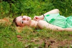 情感金发碧眼的女人,微笑秘密审议,说谎在草 库存照片