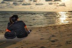 情郎一起坐海滩和观看的日落,言情 库存图片
