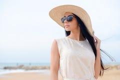 惊人一件白色礼服和太阳镜的美丽的少妇画象  库存照片
