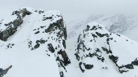 惊人巨型的山上面和小山在新鲜的粉末雪,空中射击4k包括 股票录像