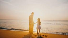 惊人的后面看法亲吻一点女儿和握手的被射击愉快的母亲在史诗金黄日落海海滩 股票录像
