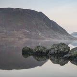 惊人的在Crummock水的冬天有雾的日出在湖区 图库摄影