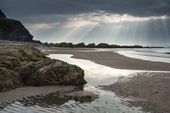 惊人的太阳发出光线破裂从在空的黄沙海滩的天空 库存照片