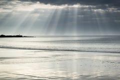 惊人的太阳发出光线破裂从在空的黄沙海滩的天空 图库摄影
