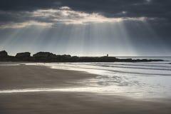 惊人的太阳发出光线破裂从在空的黄沙海滩的天空 免版税库存照片