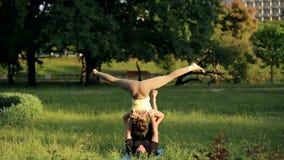 惊人的夫妇实践的acro瑜伽 专业瑜伽辅导员在城市公园实践 两成功的青年人 股票录像