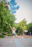 惊人的妇女让在天空的许多蓝色气球 免版税库存照片