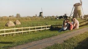 惊人的家庭在风车农场一起坐 爸爸、妈妈和孩子一起享受美妙的接合时间户外 4K 股票录像