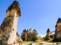 惊人的岩石烟囱形成在卡帕多细亚,土耳其,有蓝色的 库存照片