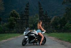 惊人的性感的女孩坐在黑白的一辆摩托车 模型在摆在一件黑球衣和牛仔布的短裤穿戴了  图库摄影