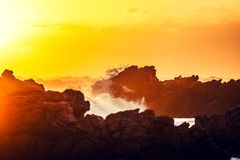 惊人的日落射击了岩石和碎波在厄加勒斯角,南非` s并且非洲` s最南端的点 免版税库存照片