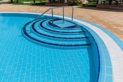 惊人的时髦的现代蓝色陶瓷砖游泳池入口,用水晶天蓝色的清楚的绿松石水 免版税库存图片