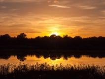 惊人的明亮的在湖水ref的秋天收获太阳设定场景 免版税库存图片