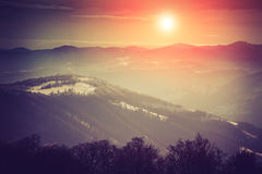 惊人的晚上冬天风景在山的 发光由阳光的意想不到的晚上 免版税库存照片