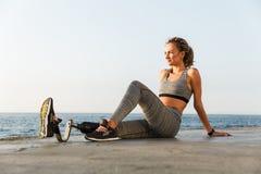 惊人的残疾体育妇女坐海滩 免版税图库摄影