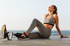 惊人的残疾体育妇女坐海滩 库存图片