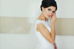 惊人的深色的新娘在绝尘室看起来嫩摆在 免版税库存照片