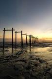 惊人的热带日落背景,在泥泞的海滩的木结构 库存图片