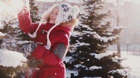 惊人的特写镜头射击了有冬天的衣裳的逗人喜爱的白种人小女孩从杉树慢动作的乐趣打的雪 影视素材