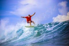 惊人的蓝色波浪的冲浪者 库存图片