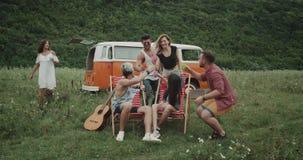 惊人的野餐,当时髦的年轻朋友,坐野餐椅子,站起来的某人,他们对负五颜六色 影视素材
