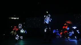 惊人的霓虹舞蹈展示由熟练的舞蹈家执行了在黑暗 股票录像