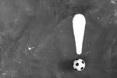 惊叹号由小橄榄球球和白色粉笔线制成在与拷贝空间的黑暗的织地不很细黑板背景 r 库存照片
