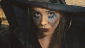 惊吓在照相机的黑外套的恶魔般女性美女 影视素材