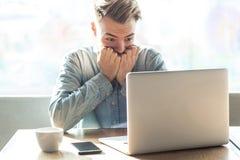 惊吓或紧张!情感紧张的年轻商人画象在蓝色衬衣的在咖啡馆工作和钉子在网上坐 免版税库存图片