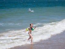 惊吓的一个小女孩和用尽海 库存照片