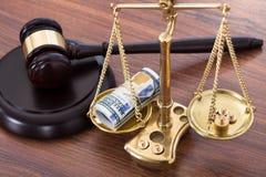 惊堂木和标度与金钱在书桌上 免版税库存图片