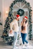 惊奇一个的人的播种的射击他的有圣诞节礼物的女朋友 免版税图库摄影