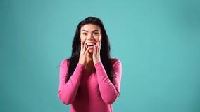 惊奇地微笑在慢动作的绿松石背景的年轻愉快的美丽的女孩 股票视频