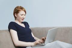 惊奇地看膝上型计算机的年轻女性 免版税库存图片