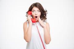 惊奇妇女谈话在电话管 免版税图库摄影