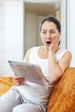 惊奇成熟妇女看报纸 免版税库存照片