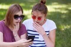 惊奇有哀怜表示的两个少妇被聚焦入手机屏幕,在互联网,穿戴时髦树荫读可怕的新闻 免版税库存图片