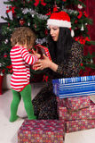 惊奇母亲和小孩开放Xmas礼物 免版税库存照片
